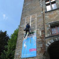 Cordiste installant un panneau publicitaire au château de Châteaubriant (44).