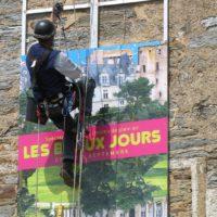 travaux en hauteur : Cordiste posant une enseigne au château de châteaubriant.